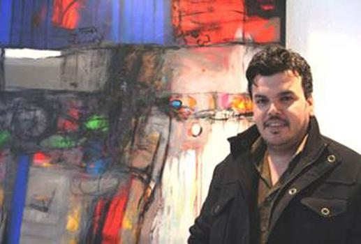 Iraqi Artist and Refugee Alaa al-Baghdadi stands in front of one of his paintings.