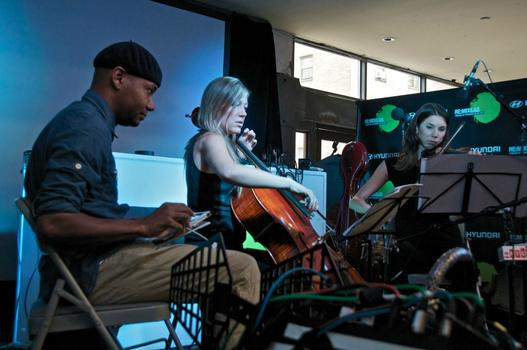 DJ Spooky performing (on iPad) with cellist Laura Metcalf and violinist Sarah Whitney