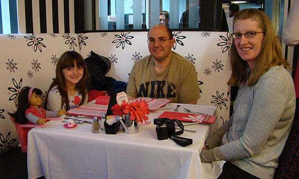 The Robinson family (Emma and her doll (also named Emma), Jeff and Christina eat at the Manhattan American Girl store. They made the trip from Stony Brook, New York.