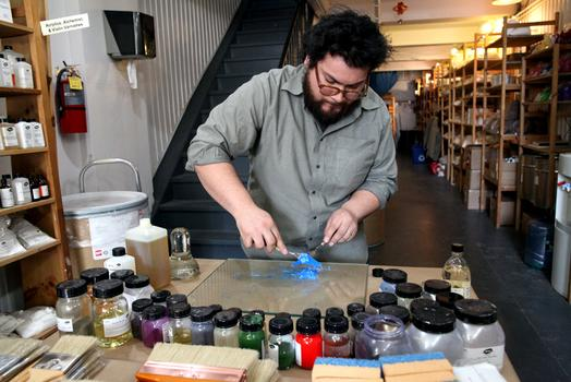 Roger Carmona mixing pigment and oil.