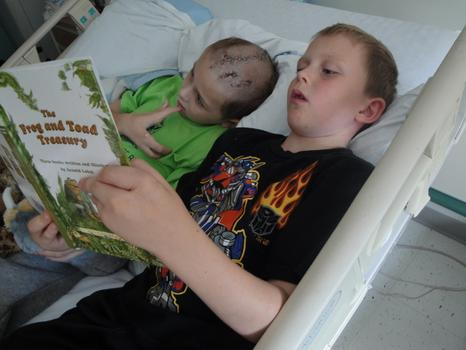 Sam's survival from the accident was narrow, and required a long hospital stay. Reading with brother Maxwell.