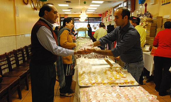 Kulwant Deol samples a chandrakalla before purchasing eight boxes of mixed rasgulla, ladoo and chandrakala to give to friends and family for Diwali.
