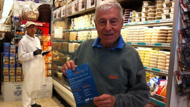 Saul Zabar, owner of Zabar's poses with a WQXR Trout Week pamphlet