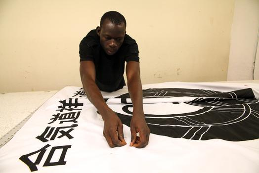 A tailor from Burkina Faso works on a banner.