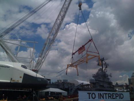 The Enterprise will be hoisted via crane onto the deck of the Intrepid.