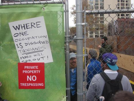 Protesters move through a hole in the fence to a new site, which is on private property.