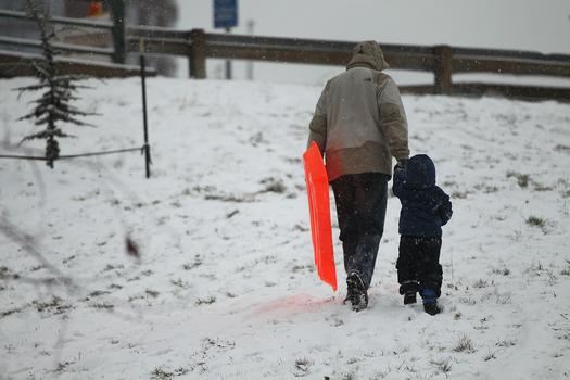 A man and child walk up a hill with a sled through the morning snow.
