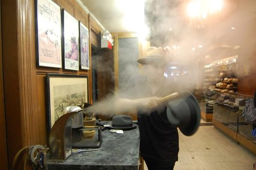 Salesman, Kevin Gerber cleans a hat with steam