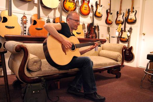 Timo Hostman, visiting New York from Finland, playing a guitar at Mandolin Brothers.