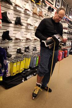 A customer tries on a new pair of ice hockey skates at Westside Skate and Stick.