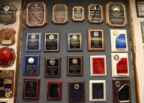 A wall of plaques at Trophy World.