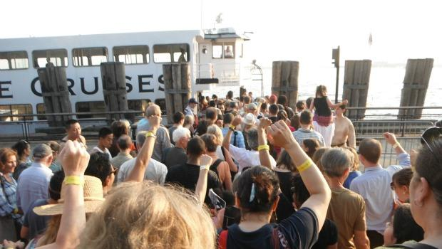 Audience members file onto the ferry that takes them to Governor's Island, yellow wristbands in the air.
