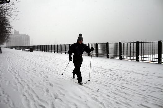 A woman uses cross country skis in the morning snow along the Brooklyn Heights Promenade on January 21, 2012.