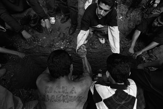 Donna De Cesare. San Salvador, El Salvador 1996. Gang members make a pact of revenge over the grave of a slain  leader.