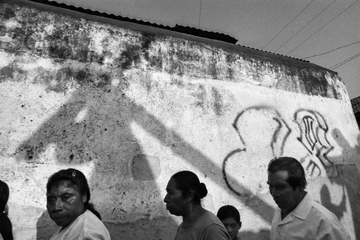 Donna De Cesare. Jocotenango, Guatemala 2001. A Holy Week procession passes village walls marked with the graffiti of the gang that dominates the zone.