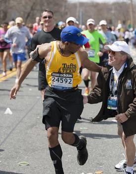 A member of the Tufts marathon team greets coach Megerle.