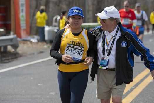 A member of the Tufts marathon team with coach Megerle