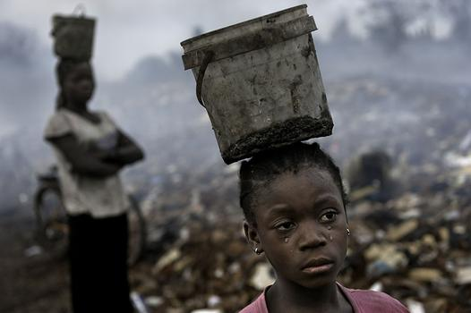 In an e-waste dump in that kills nearly everything that it touches, Fati, 8, works with other children searching through hazardous waste in hopes of finding whatever she can to exchange for pennies.