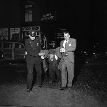 "Man being dragged by cops at night still from John Maloof and Charlie Siskel's ""Finding Vivian Maier."""