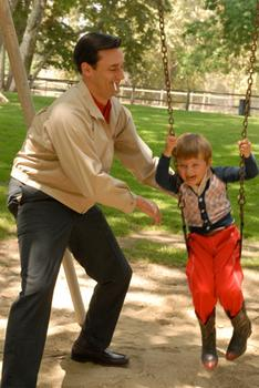 "Don Draper from AMC's ""Mad Men"", pushing his son, Bobby, on a swing"