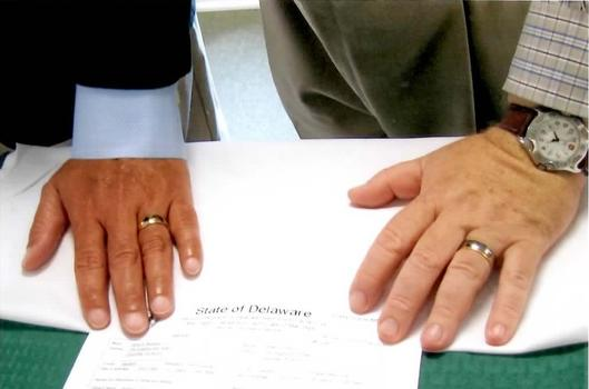 David Michener and Bill Ives place their hands on their marriage certificate.