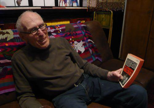 Barney Rosset holds his personal first-edition paperback of <em>The Autobiography of Malcolm X</em>.