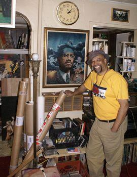Artist Charles Lilly stands next to his famous painting of Malcolm X.  The painting is featured on the Ballantine paperback edition of <em>The Autobiography of Malcolm X</em>.