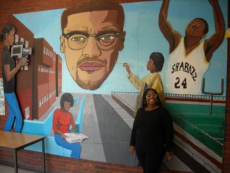 Teacher Lauretta Crawford poses in front of a mural at Malcolm X Shabazz High School.