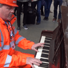 A traffic marshal in London's St Pancras Station surprises travelers with a quick turn on a public piano.