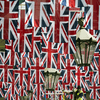 A construction worker stands on a platform amongst the Union Flags in the rafters of Covent Garden installed in honour of the Queen's Diamond Jubilee in London on May 30, 2012.