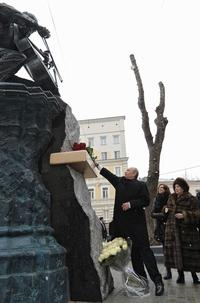 Vladimir Putin lays flowers at a monument to Mstislav Rostropovich on Moscow, on March 29, 2012, with the cellist's widow, Galina Vishnevskaya (R) and daughter, Elena Rostropovich (2R)