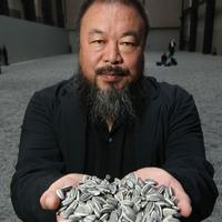Chinese Artist Ai Weiwei holds some seeds from his Unilever Installation 'Sunflower Seeds' at The Tate Modern.