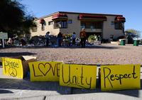 TUCSON, AZ - JANUARY 12: People look at a makeshift memorial outside the office of Rep. Gabrielle Giffords (D-AZ) on January 12, 2011