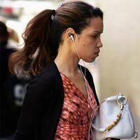 A woman walks down the street listening to an iPod