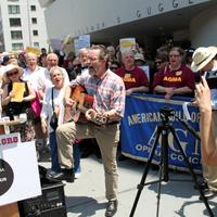 Union members sing protest songs outside the City Opera press conference