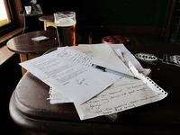 Songwriting, pieces of paper, writing, pen.