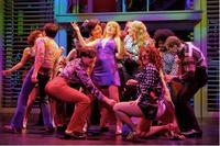 Connie Bradshaw (Julie Reiber, center, purple dress) gives newcomer Mary Ann Singleton (Betsy Wolfe, center, blue shirt) a taste of the big city in a disco.