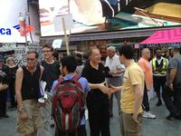 Choral conductor Kent Tritle (center) welcomes singers as part of the 'flash choir' in Times Square on June 21, 2012.