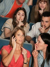 Audiences shush a woman taking a call at a concert