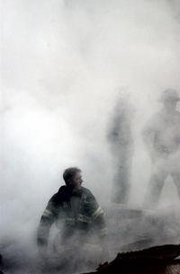 This US Navy photo released 17 September, 2001, shows a firefighter emerging from the smoke and debris of the World Trade Center September 14, 2001.