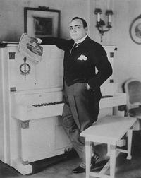 Enrico Caruso standing by his piano