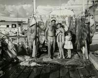A proud fishing family in 1958 stands before several prizewinning fish much bigger than a human five-year-old