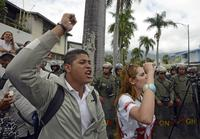 People shout slogans as they protest against the government of Venezuelan President Nicolás Maduro in front of riot policemen outside the Cuban embassy in Caracas on February 25, 2014