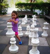 Child playing with large chess pieces