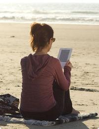 reading a Kindle on the beach