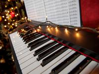 A piano with christmas lights and tree.