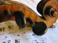 A violin rests on a sheet of music.