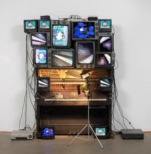 "Nam June Paik's ""Untitled,"" 1993. Player piano, fifteen televisions, two cameras, two laser disc players, one electric light, light bulb, wires, laser disc player and lamp. Nam June Paik"