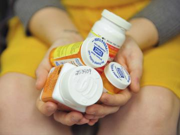 Heidi Wyandt, 27, holds a handful of her medication bottles at the Altoona Center for Clinical Research in Altoona, Pa., on Wednesday, March 29, 2017.