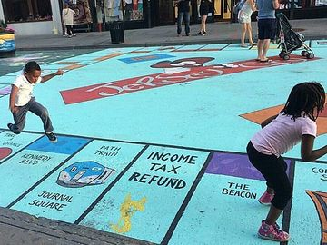Kids enjoying a Monopoly board mural in Jersey City before it was painted over.